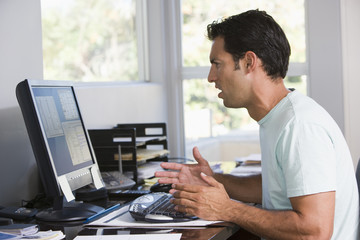 Man in home office using computer looking frustrated