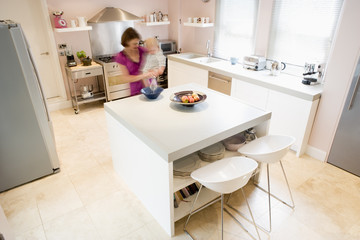 Woman in kitchen whisking on counter holding baby