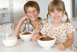 Fototapety Two young children in kitchen eating cereal smiling
