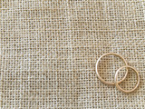 Two golden rings at the linen background poster