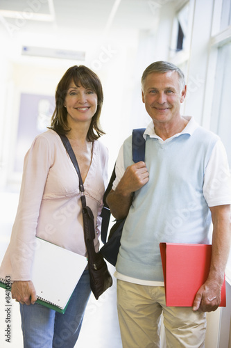 A man and woman with backpacks standing on a campus