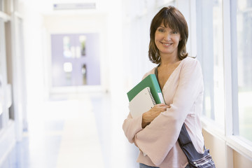 A woman with a backpack standing in a campus corridor