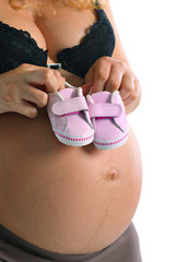 Pregnant woman with little baby shoes on her belly