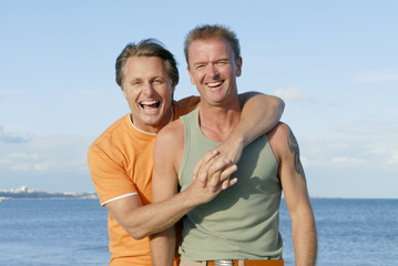 A gay couple having fun on the beach together.