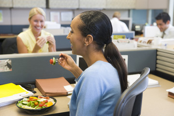 Businesswoman in cubicle eating salad