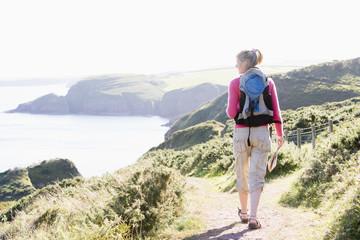 Woman walking on cliffside path
