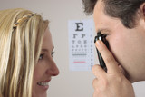 Female patient getting an eye checkup poster