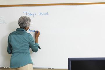 Female teacher writing on whiteboard in classroom