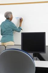 Female teacher writing on whiteboard in computer classroom