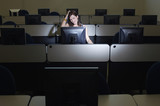 Female student with hand on head in computer classroom