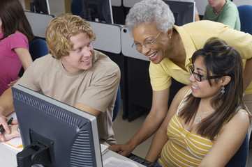 Teacher helping two students working in computer classroom