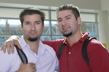 Two male student embracing, indoors, portrait