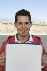 Portrait of young man holding sign outdoors
