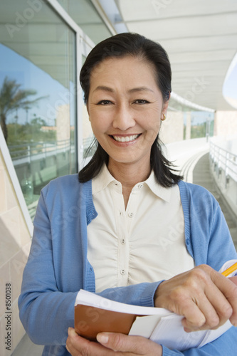 Woman holding book at school, smiling, portrait