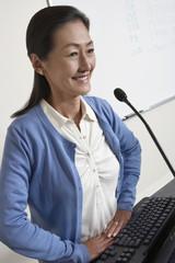 Female teacher smiling in lecture theatre