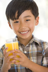 Young boy indoors drinking orange juice smiling