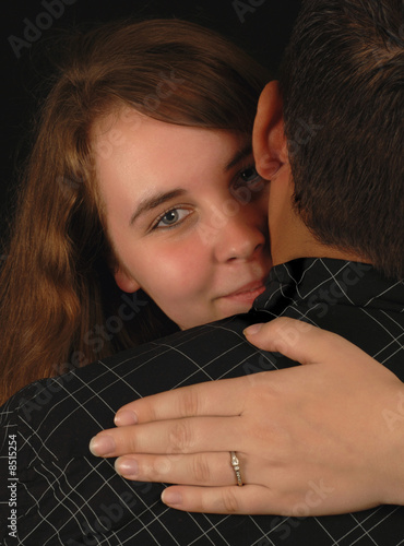 young engaged woman with arms around shoulders of man