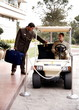 Bellboy driving hotel cart to deliver luggage to doorman