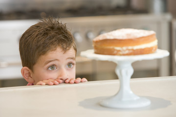 Young boy looking at cake on counter