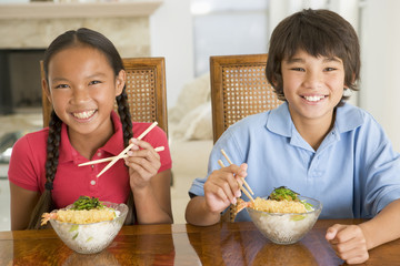 Two young children eating Chinese food in dining room