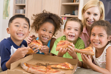 Four young children with woman eating pizza smiling