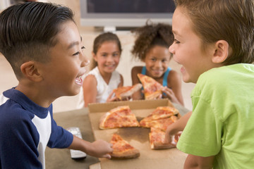 Four young children eating pizza smiling