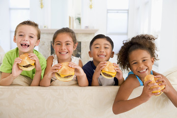 Four young children eating cheeseburgers smiling