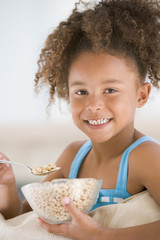 Young girl eating cereal smiling