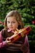 Kind mit Weihnachtsgeschenk vor Weihnachtsbaum