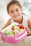 Fototapety Young girl holding packed lunch in living room smiling