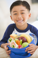 Young boy with packed lunch smiling