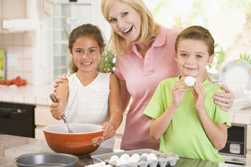 Woman and two children baking and smiling