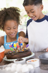 Two children with birthday cake smiling