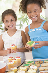 Two girls in kitchen decorating cookies smiling