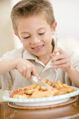 Young boy eating fish and chips smiling