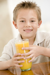 Young boy with orange juice smiling