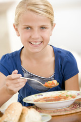 Young girl eating soup smiling