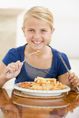 Young girl eating fish and chips smiling