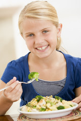 Young girl eating pasta with brocolli smiling