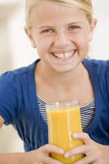 Young girl drinking orange juice smiling