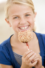 Young girl eating candy apple smiling