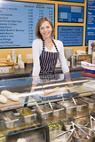 Fototapety Woman standing at counter in restaurant smiling