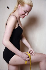 Woman measuring her thigh
