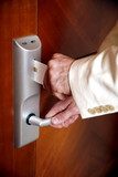 Man putting card key into hotel room door