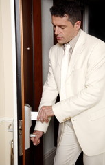 Man putting card key into hotel room door