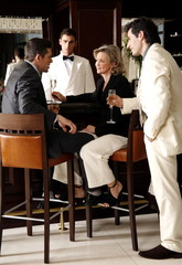 Two men and a woman sitting at a bar drinking