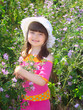 Little girl on a glade. Girl with a hat. Glade of violet flowers