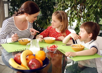 Mother and children eating breakfast