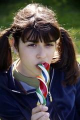 Teenage girl  licking a lollipop