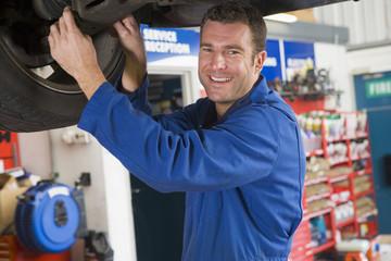 Mechanic working under car smiling